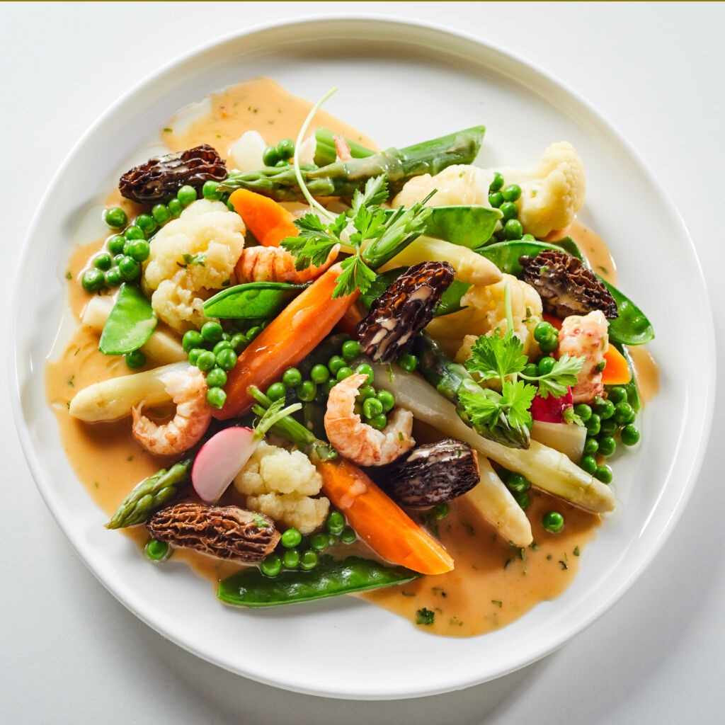 Speciality salad Leipziger Allerlei with morel mushrooms, shrimps and asparagus served with petit pois peas, carrots, cauliflower and coriander drizzled with a savory dressing