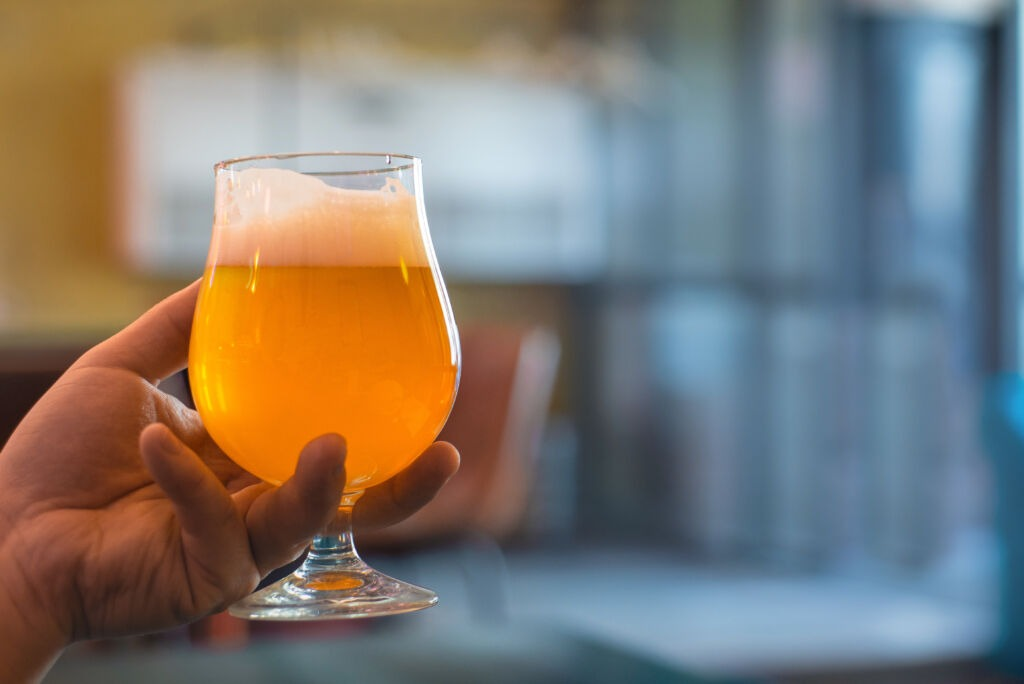 man holds in his hand a glass of craft beer